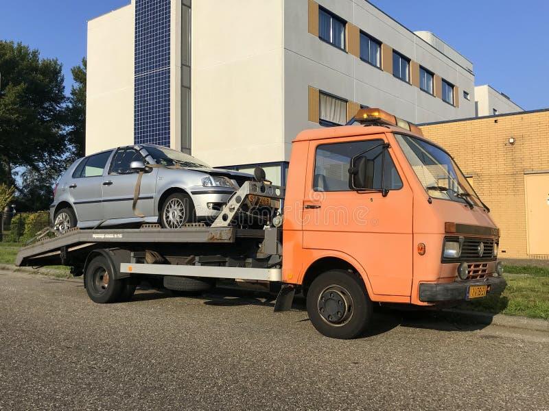Skadad bil på en plattform av en bärgningsbil arkivfoto