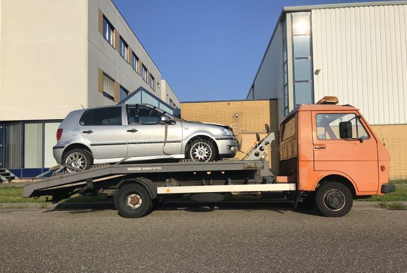 Skadad bil på en plattform av en bärgningsbil arkivfoton