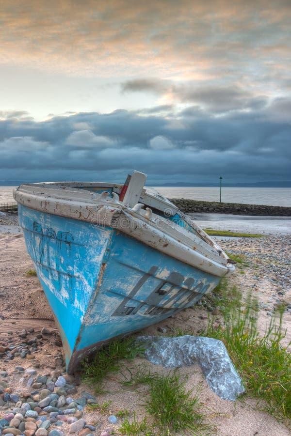 Skadad fiskebåt på den tomma stranden royaltyfri bild