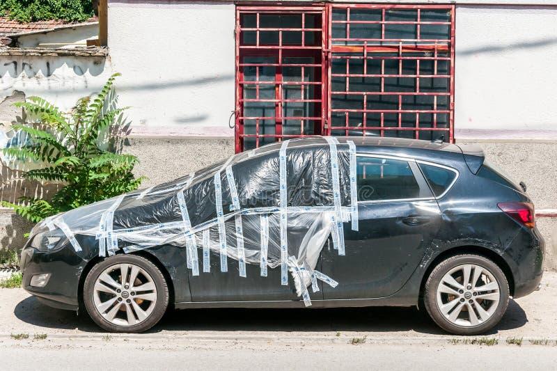 Skadad ny svart Opel Astra J halvkombi som parkeras på gatan som täckas och skyddas med nylon över den brutna vindrutan från rai arkivfoto