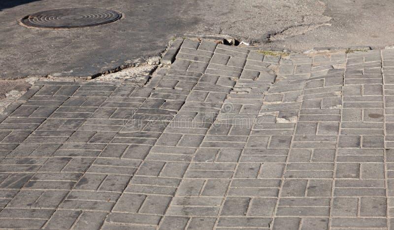 Skadad väg med potholer, orsakad av cykler med frysanläggning på vintern Dålig väg Brutna trottoarer på sidpromenader beläggning royaltyfri fotografi