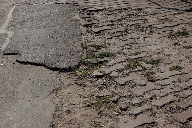 Skadad väg med potholer, orsakad av cykler med frysanläggning på vintern Dålig väg Brutna trottoarer på sidpromenader beläggning arkivfoto