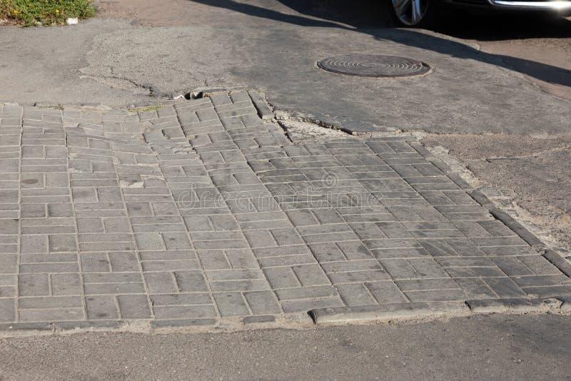 Skadad väg med potholer, orsakad av cykler med frysanläggning på vintern Dålig väg Brutna trottoarer på sidpromenader beläggning arkivfoton