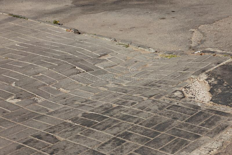 Skadad väg med potholer, orsakad av cykler med frysanläggning på vintern Dålig väg Brutna trottoarer på sidpromenader beläggning royaltyfria foton