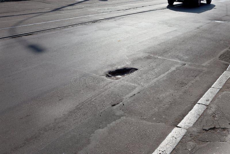 Skadad väg, sprucken asfaltskocka med potholar och lappar, Ukraina Mycket dålig väg med stora hål fruktansvärd royaltyfri bild
