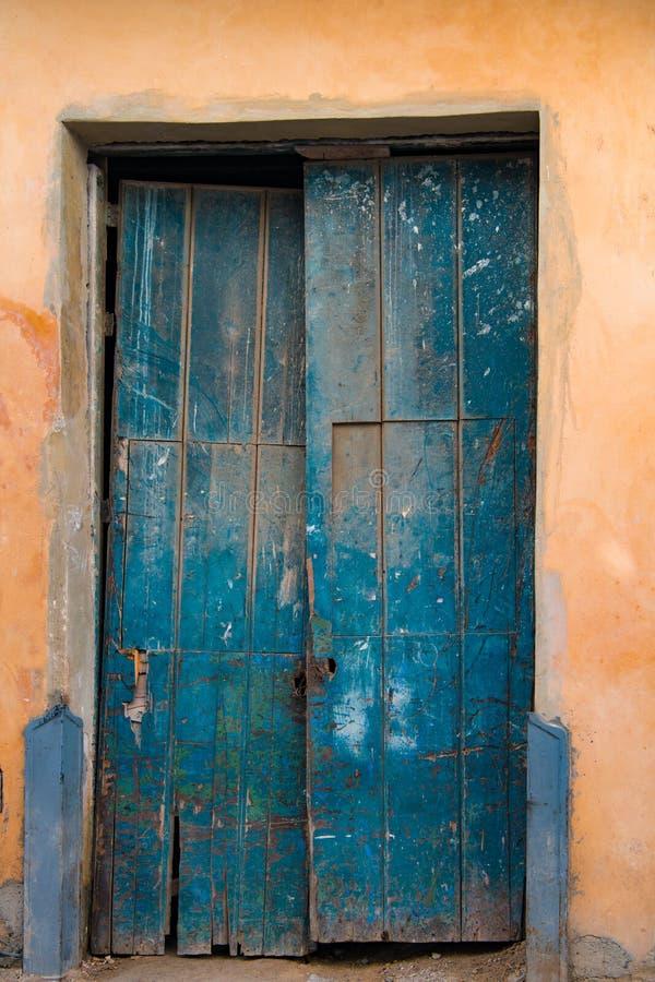 Skadlig gammal blå trädörr, havannacigarr, Kuba arkivbilder