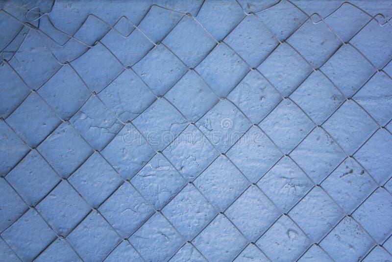 Skadlig metall som var netto på en blå vit grå sjaskig smutsig vägg, knäckte Textur för grov yttersida arkivbild