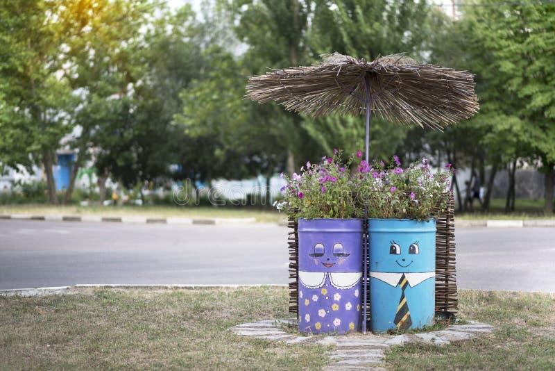 Skadovsk, de Oekraïne - Juni 23, 2017: Twee schilderden vaten met bloemen onder de paraplu, buitenkant tegenover de koffieemmer,  stock foto