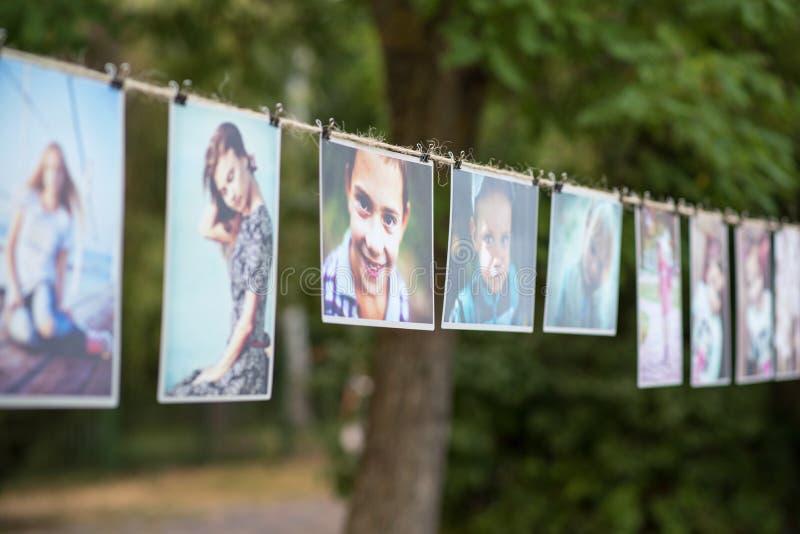 Skadovsk Ukraina - Juni, 2017: Uppsättning av utskrivavna fotografier av folk som hänger på kabeln fotografering för bildbyråer
