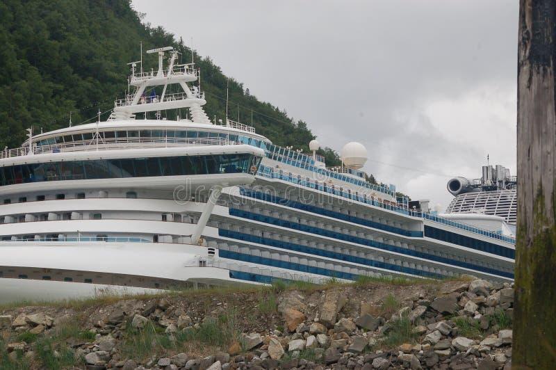 SKAGWAY, ALASKA, EL 26 DE JUNIO DE 2012: Princesa barco de cruceros atracado delante de las montañas capsuladas nieve fotos de archivo