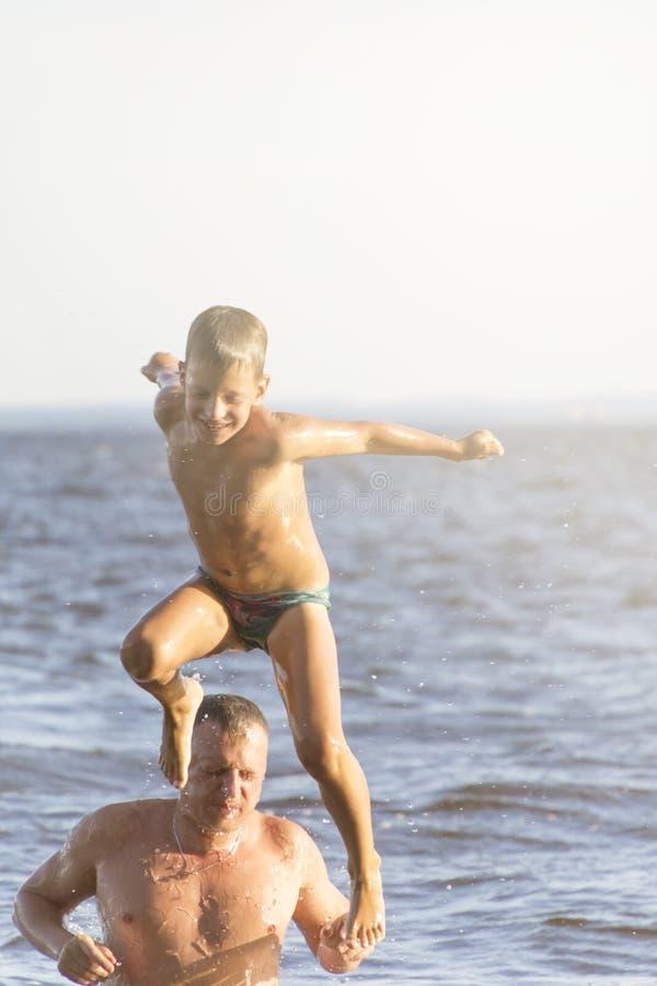 Skakać w wodzie Mężczyzna i chłopiec mamy zabawę i bryzgamy w wodzie plażowego brytyjskiego pojęcia wakacyjna paszportowa lato za obraz royalty free