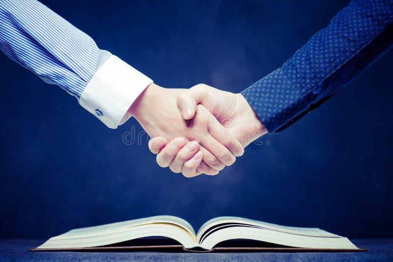 Skaka händer på öppna böcker royaltyfri bild