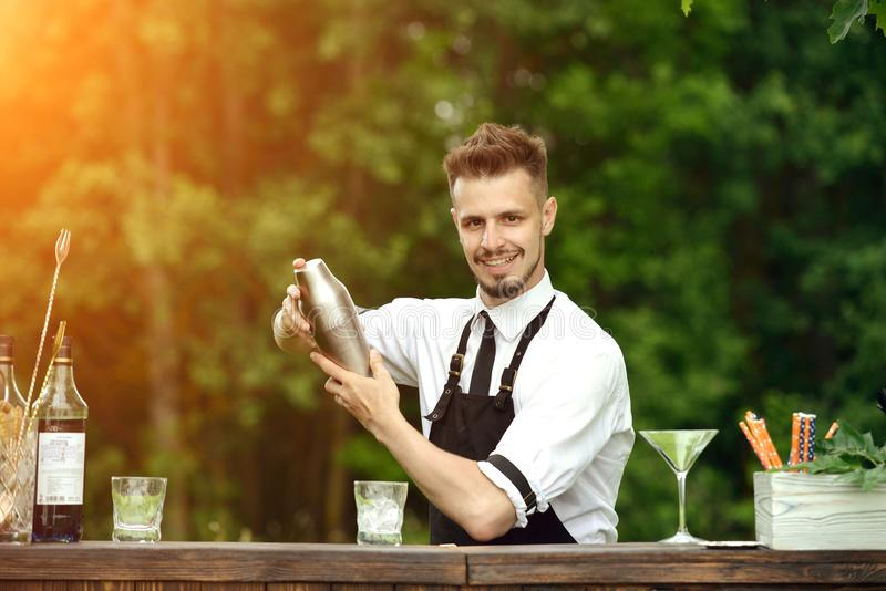 Skaka och blandande coctail för stilig le bartender utomhus, ca royaltyfria foton