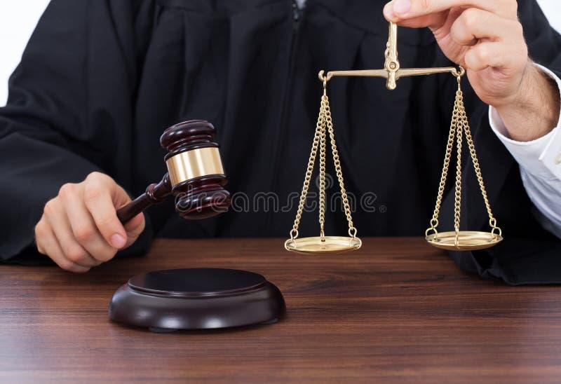 Skala för domareinnehavvikt, medan slå auktionsklubban på skrivbordet royaltyfri foto