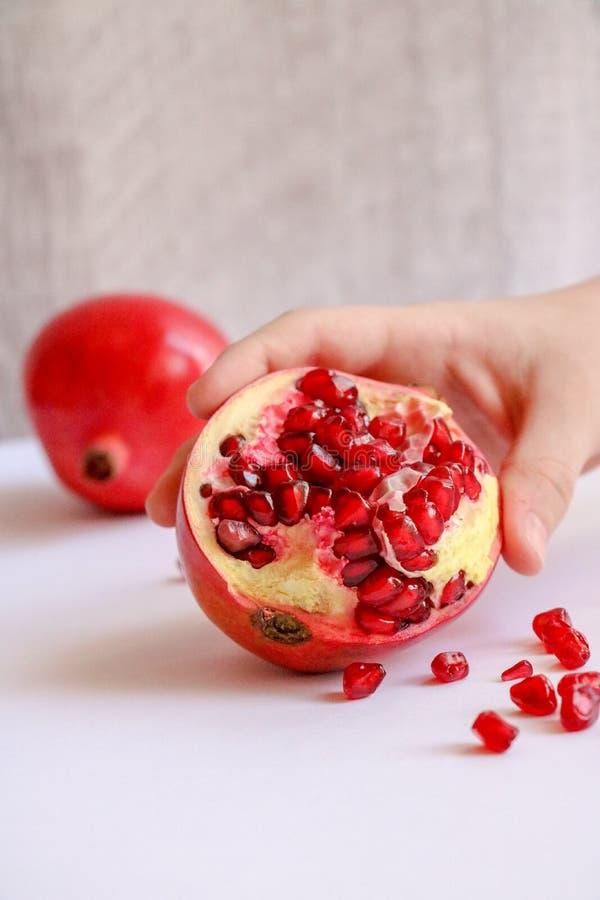 Skalad granatäpple i barnens hand arkivbild