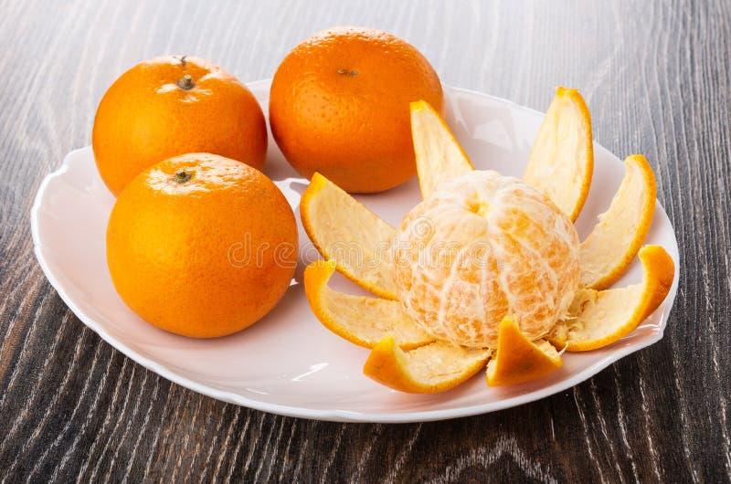 Skalad tangerin, unpeeled tangerin i maträtt på den mörka trätabellen royaltyfri fotografi