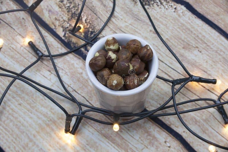 skalade hasselnötter i en bunke på texturerad träbakgrund, bästa sikt med ljus royaltyfri bild