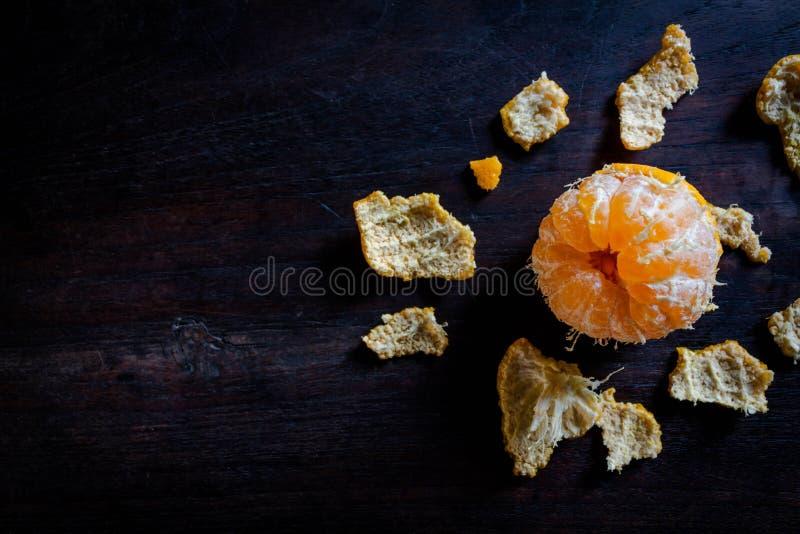 Skalade tangerin på den mörka trätabellen royaltyfria foton
