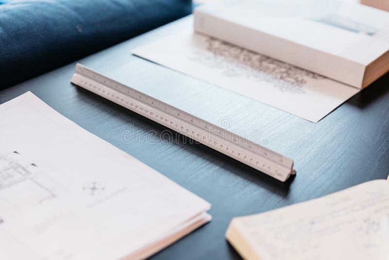 Skalalinjalställe under av den designteckning, böcker och anteckningsboken på trätabellen Arkitekt och m?rkes- bakgrund med kopie arkivbilder