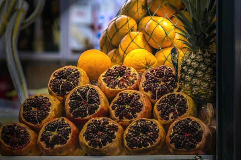 Skalat från bästa granatäpplen, fulla apelsiner och en ananas som väntar för att pressas för fruktsaft royaltyfri foto