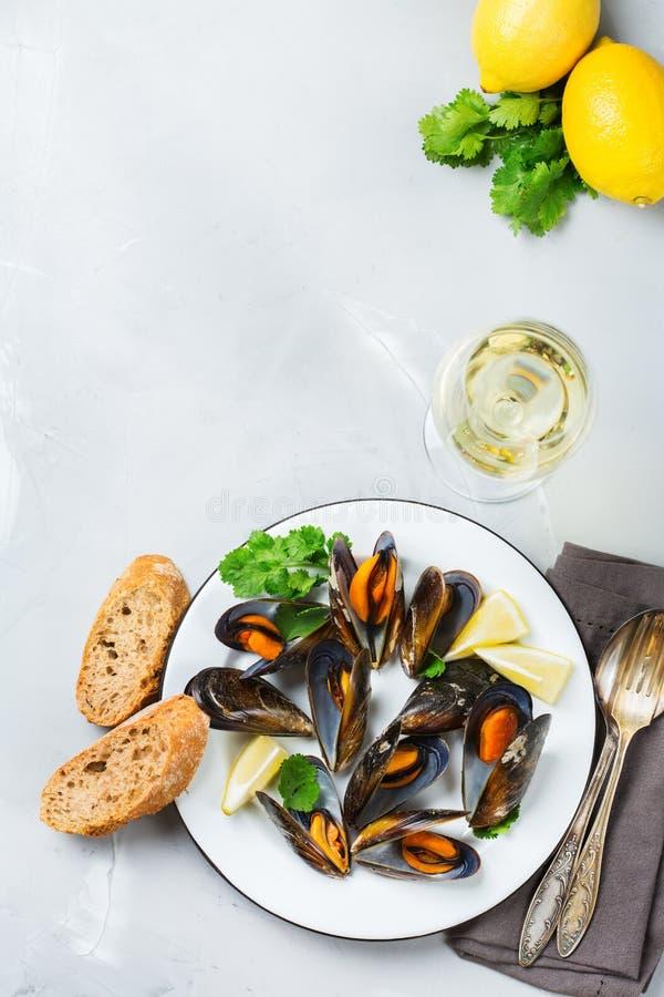 Skaldjurmusslor med vitt vin, skaldjur på en tabell royaltyfri foto