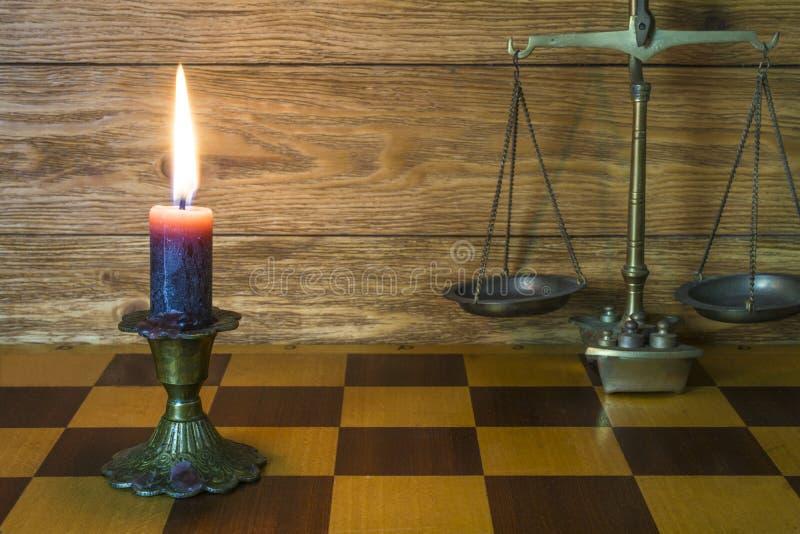 Skale od brązu, przeciw świeczki rażący stojaki na szachownicy fotografia stock