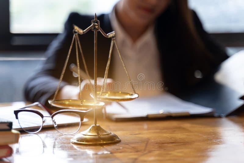 Skalen von Gerechtigkeit auf Holztischhintergrund mit den professionellen weiblichen Rechtsanwälten, die an den Sozietäten arbeit stockbild