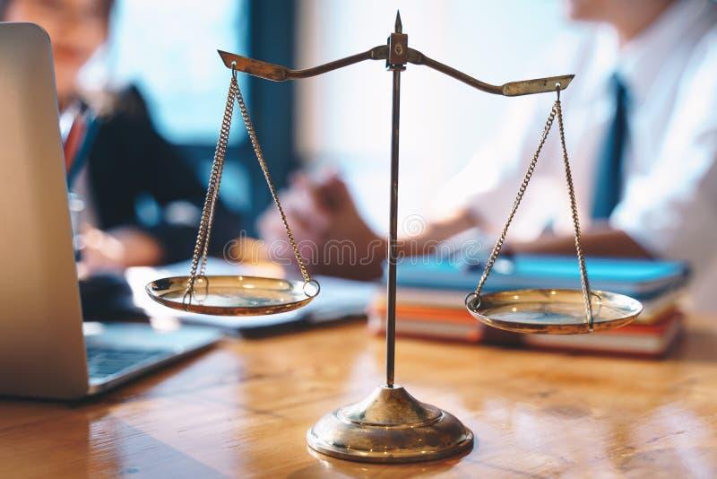 Skalen von Gerechtigkeit auf Holztischhintergrund mit der Geschäftsfrau und männlichen Rechtsanwälten, die Vertragspapiere an den stockfoto