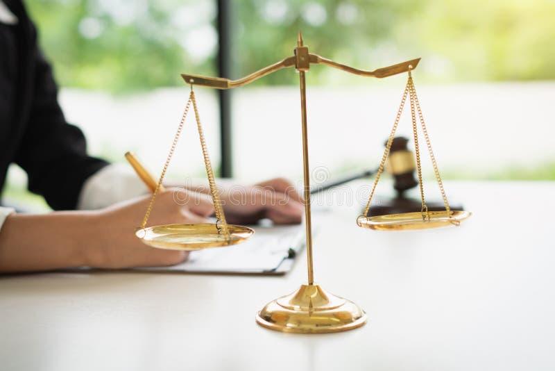 Skalen von Gerechtigkeit auf weißem Tabellenhintergrund mit den weiblichen Rechtsanwälten, die an den Sozietäten arbeiten lizenzfreies stockfoto