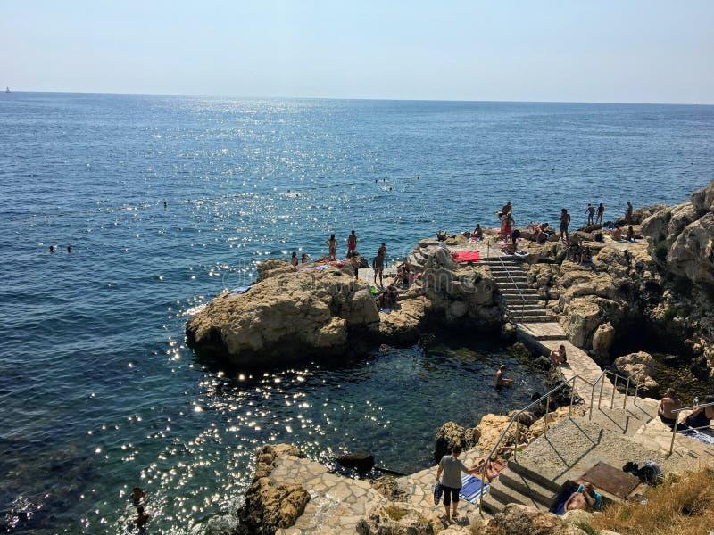 On skaliści brzeg stary miasteczko Rovinj, Chorwacja wzdłuż Adriatyckiego morza Miejscowi i turyści pływają fotografia stock