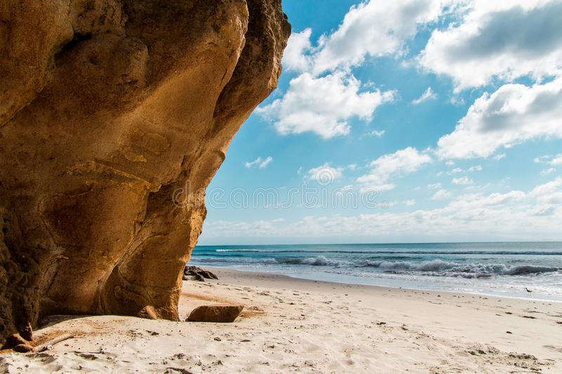 Skalista faleza na wzdłuż plaży w słonecznym dniu z niebieskimi niebami obraz stock