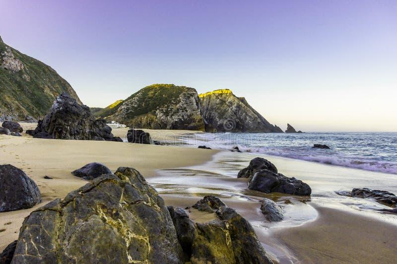 Skalista i piaskowata plaża przy wschód słońca, Portugalia zdjęcia stock