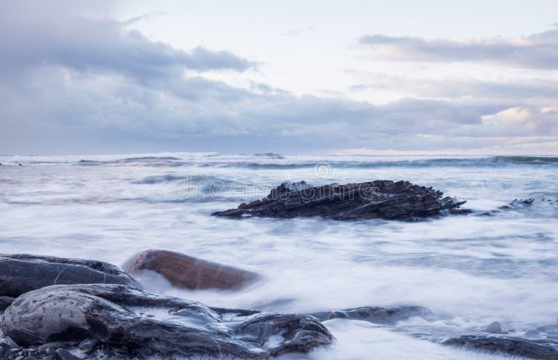 Skalista linia brzegowa w kraju baskijskim pod burzliwym niebem zdjęcia stock