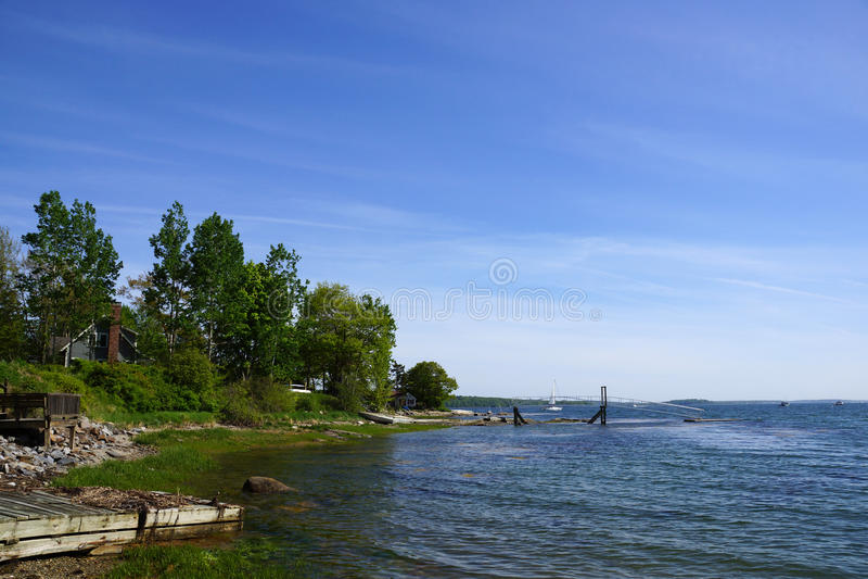 Skalista linia brzegowa z molem w odległości i zieleni drzewach zdjęcie royalty free