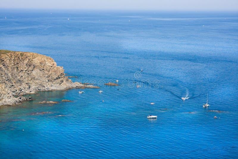 Skalisty brzeg i jachty w żołnierz piechoty morskiej rezerwie Cerbere Banyuls, morze śródziemnomorskie, Pyrenees Orientales, Cote obraz stock