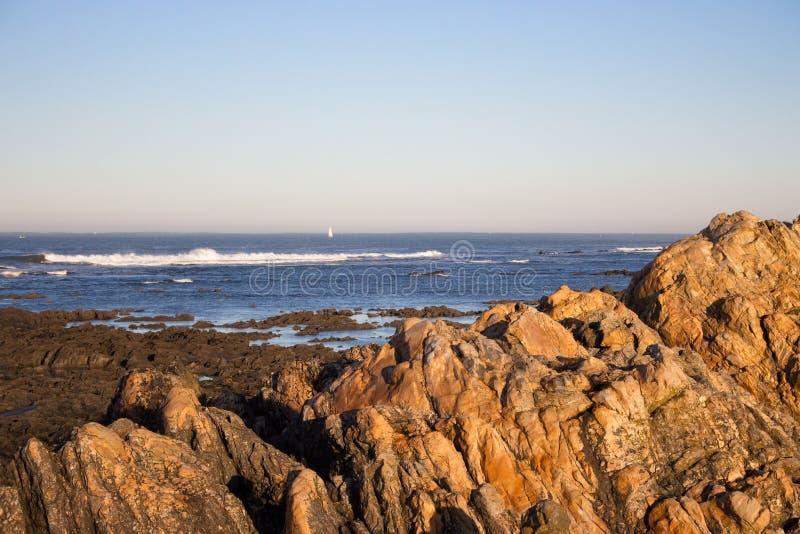 Skalisty oceanu wybrzeże z białym żeglowanie statkiem na horyzoncie w ranku ranek pi?kny seascape zdjęcia royalty free