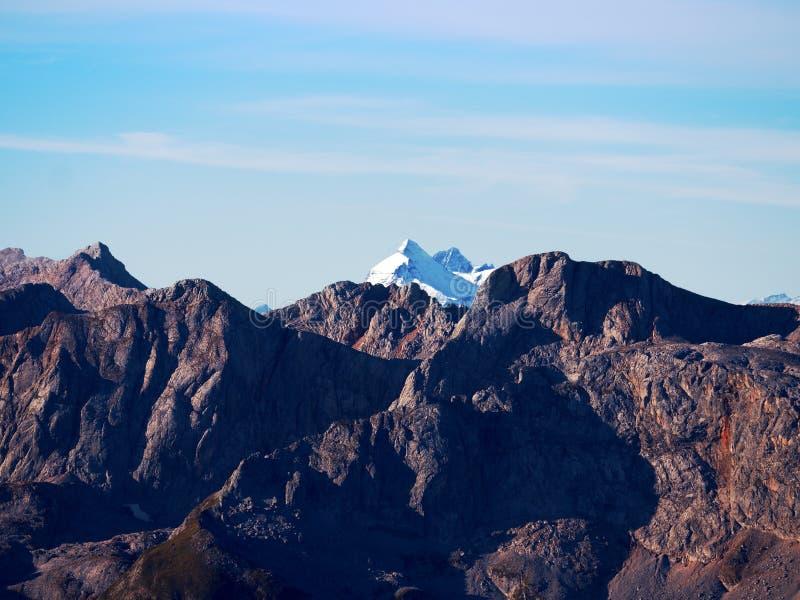Skalisty szczyt Alps halni w słonecznym dniu Skała pod świeżym prochowym śniegiem obrazy stock