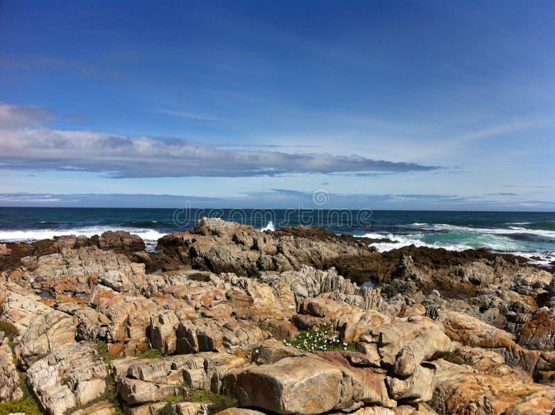 Skalisty widok na ocean z Jasnymi niebieskimi niebami zdjęcie stock
