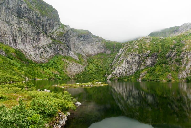 Skalisty wybrzeże w mgle na jeziornym Hamnoyvatnet, Lofoten, Norwegia zdjęcie stock