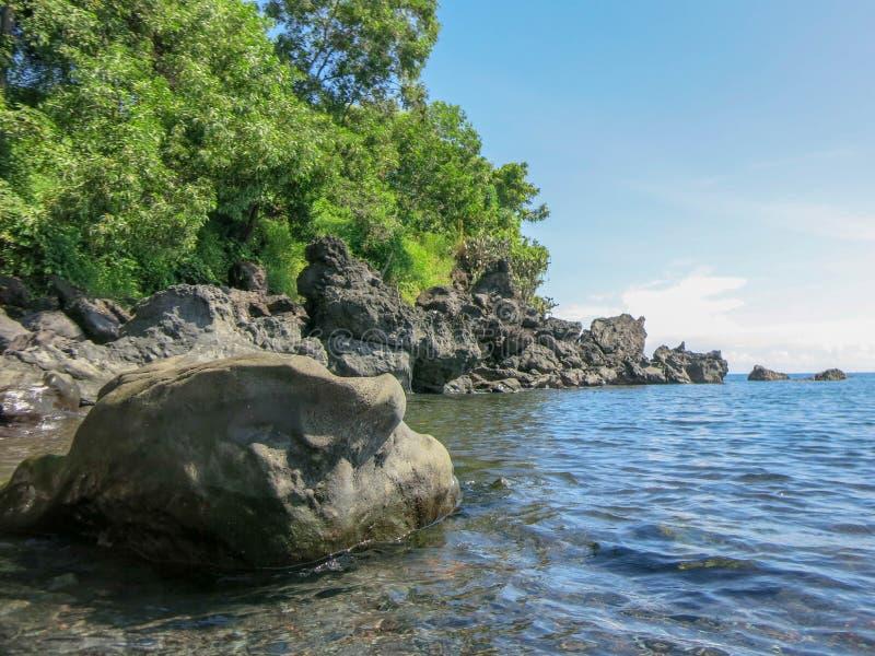Skalisty wybrzeże z tropikalną roślinnością Falezy sterczy nad powierzchnia Spokojny morze i nasłoneczniona linia brzegowa obrazy royalty free