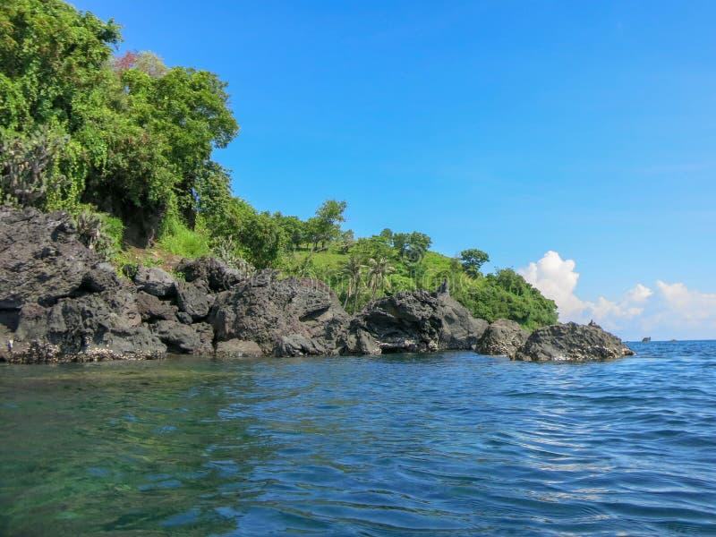 Skalisty wybrzeże z tropikalną roślinnością Falezy sterczy nad powierzchnia Spokojny morze i nasłoneczniona linia brzegowa fotografia stock