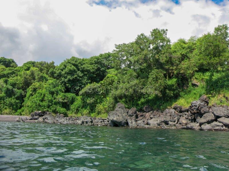Skalisty wybrzeże z tropikalną roślinnością Falezy sterczy nad powierzchnia Spokojny morze i nasłoneczniona linia brzegowa zdjęcia stock