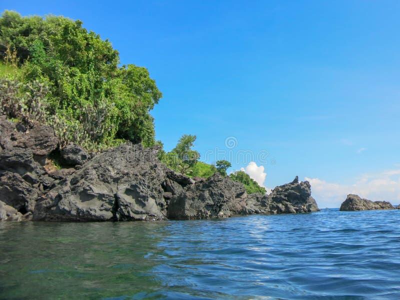 Skalisty wybrzeże z tropikalną roślinnością Falezy sterczy nad powierzchnia Spokojny morze i nasłoneczniona linia brzegowa zdjęcia royalty free