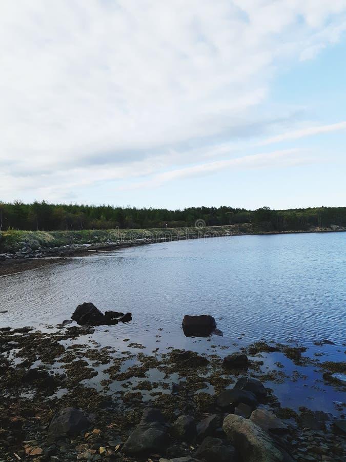 Skalisty wybrzeże zatoka przy zmierzchem z chmurnym niebem obrazy stock