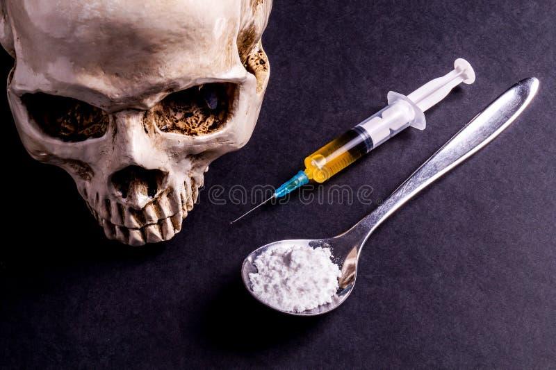 Skalle, injektionsspruta och droger på en sked royaltyfria bilder