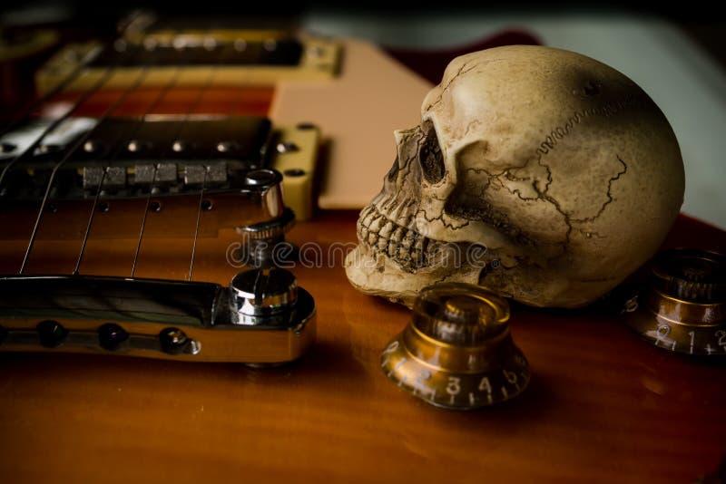 Skalle och elektrisk gitarr arkivbilder