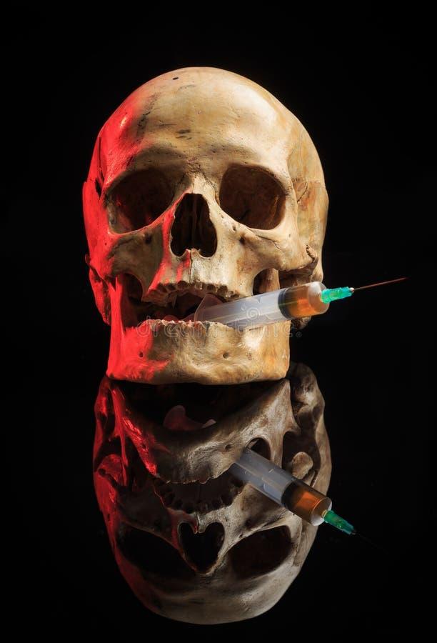 Skalle och injektionsspruta av gulaktig flytande Begrepp royaltyfria foton