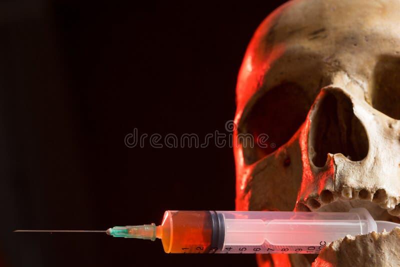 Skalle och injektionsspruta av gulaktig flytande Begrepp arkivbilder