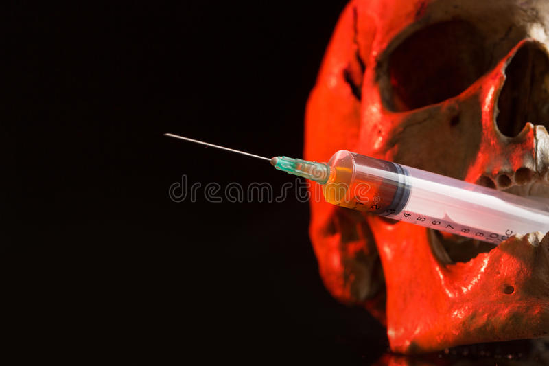 Skalle och injektionsspruta av gulaktig flytande Begrepp royaltyfri foto