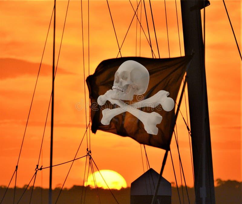 Skallen och korslagda benknotor som flaggan flyger över, piratkopierar skeppet på öporten arkivbild